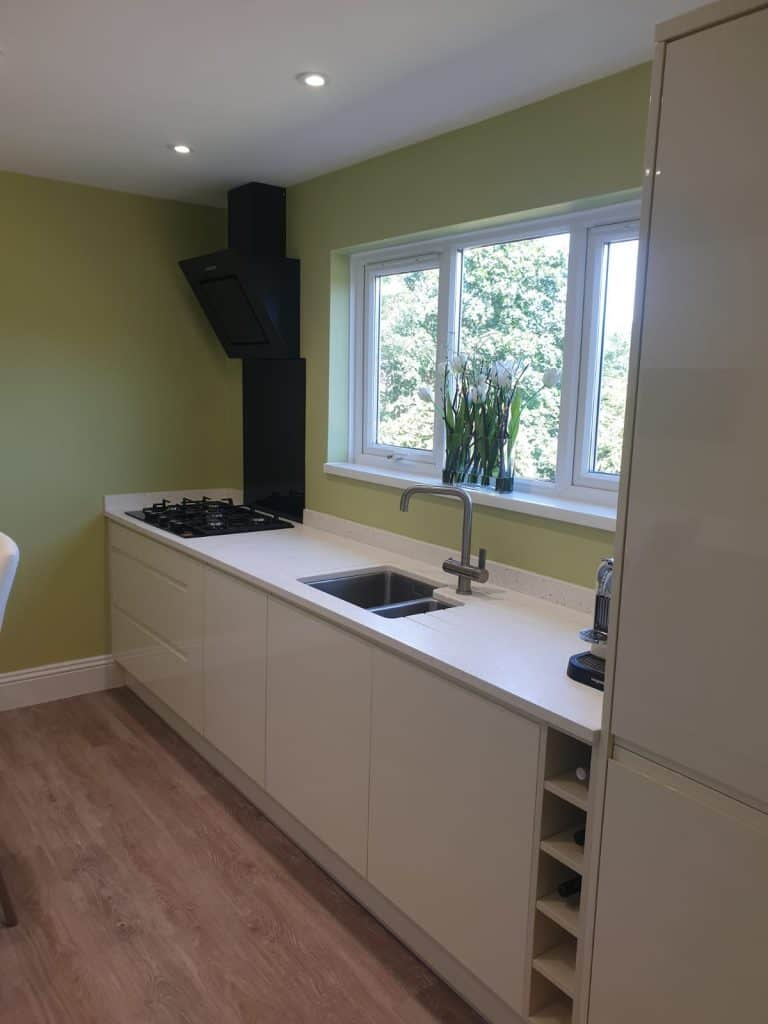 White Acrylic worktops with an under mounted stainless steel sink and brushed steel tap, along with an angled Samsung extractor in black, a black Glass splash back and a black Samsung gas on glass hob. Crown Lifestyle Nova J handle-less door in Oyster